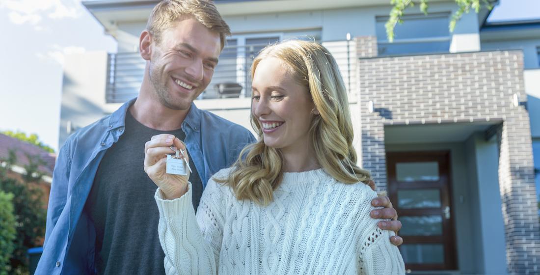 Jeune couple avec clé en main devant la nouvelle maison qu'ils ont achetée