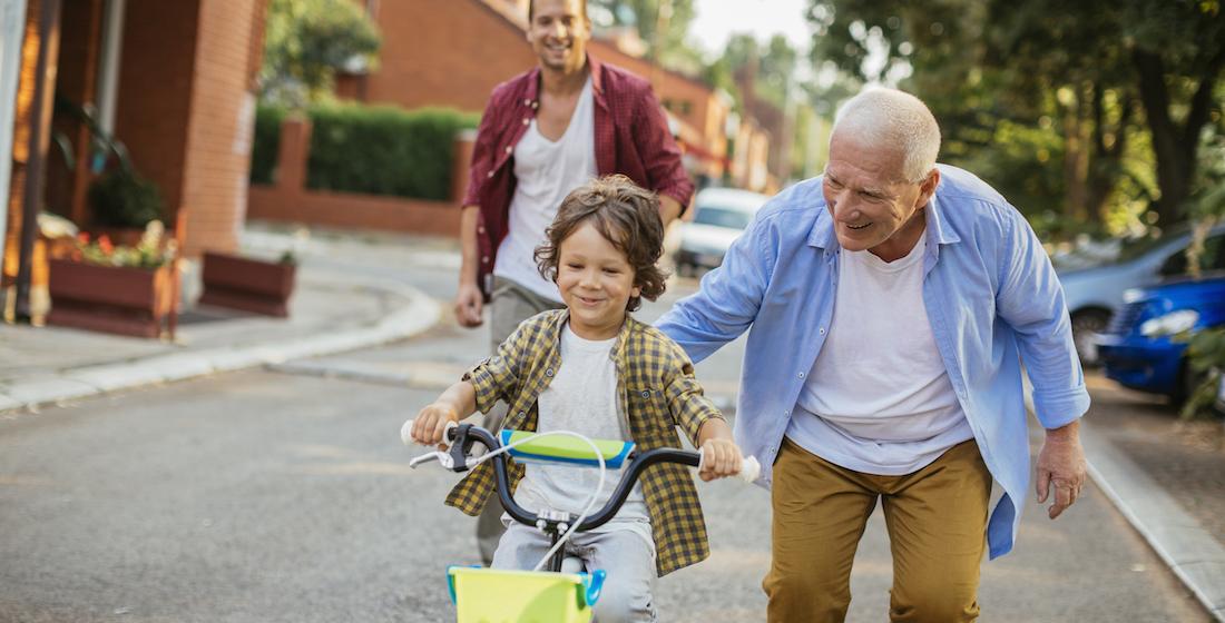 Jeune garçon apprenant à conduire un vélo avec l'aide de son grand-père et de son père